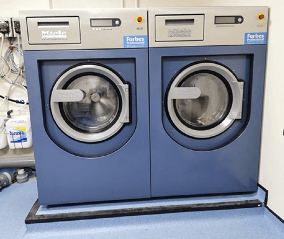 Two blue Miele's 13kg PW413 commercial machines in NHS premise